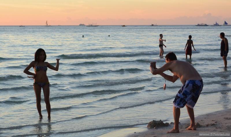 Люди фотогрфируют белый пляж на закате
